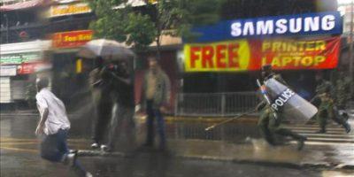 Agentes de la policía antidisturbios (d) persiguen a un partidario del derrotado candidato presidencial y saliente primer ministro Raila Odinga (i). EFE