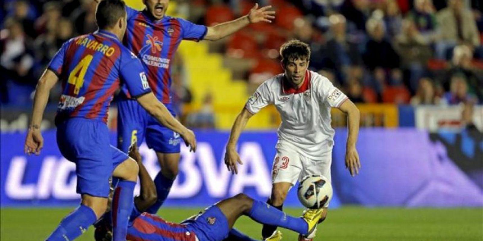 """El defensa del Sevilla FC, Jorge Andujar """"Coke"""" (d), se lleva el balón ante los jugadores del Levante, durante el encuentro correspondiente a la jornada 29 de primera división. EFE"""