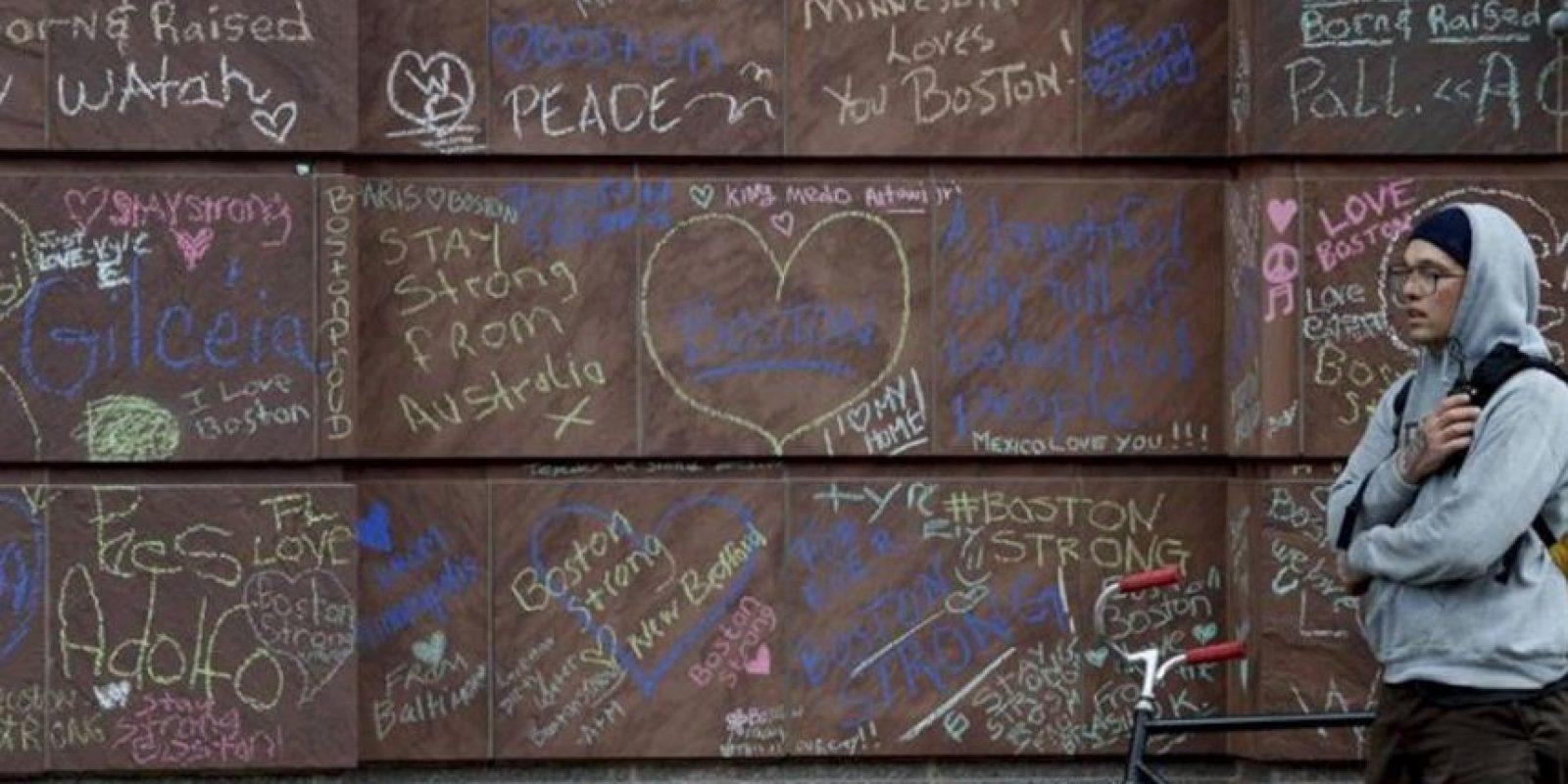 Un joven permanece en pie junto a un muro en el que hay escritas palabras de recuerdo hacia las víctimas de los atentados de Boston, en Boston, Massachusetts, Estados Unidos. EFE