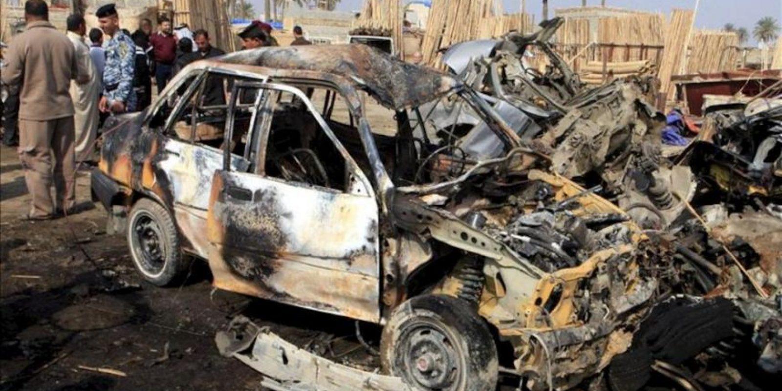 Varios iraquíes congregados junto a varios vehículos destruidos tras un atentado con coche bomba registrado en el barrio de Al Kazemiya, de mayoría chií y ubicada en el norte de Bagdad (Irak), el pasado 8 de febrero. EFE/Archivo