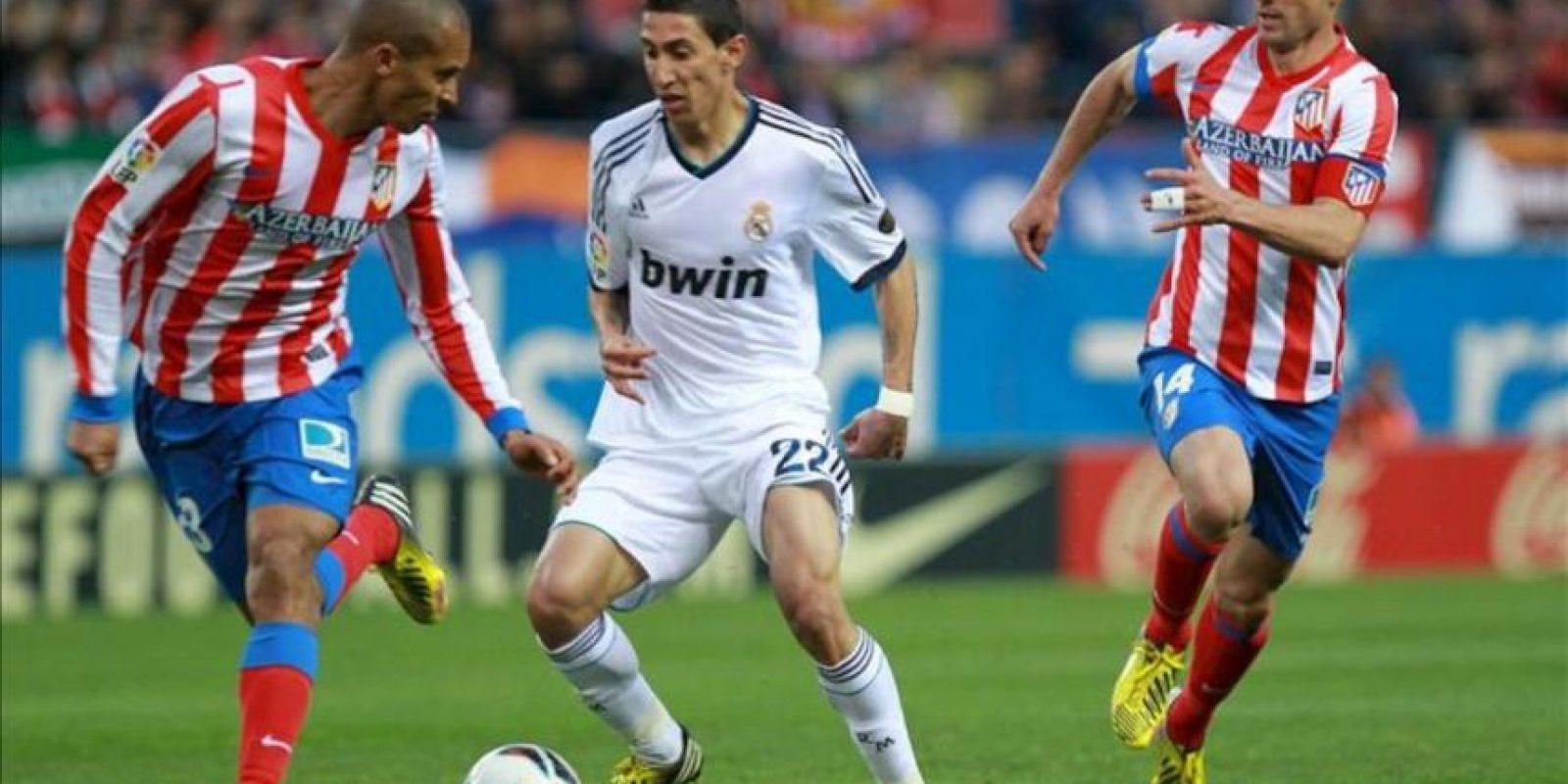 El centrocampista argentino del Real Madrid Angel di Maria (c) controla el balón ante los jugadores del Atlético de Madrid Joao Miranda (i) y Gabi Fernández en el partido de la trigésima tercera jornada de liga en Primera División que se disputó en el estadio Vicente Calderón. EFE