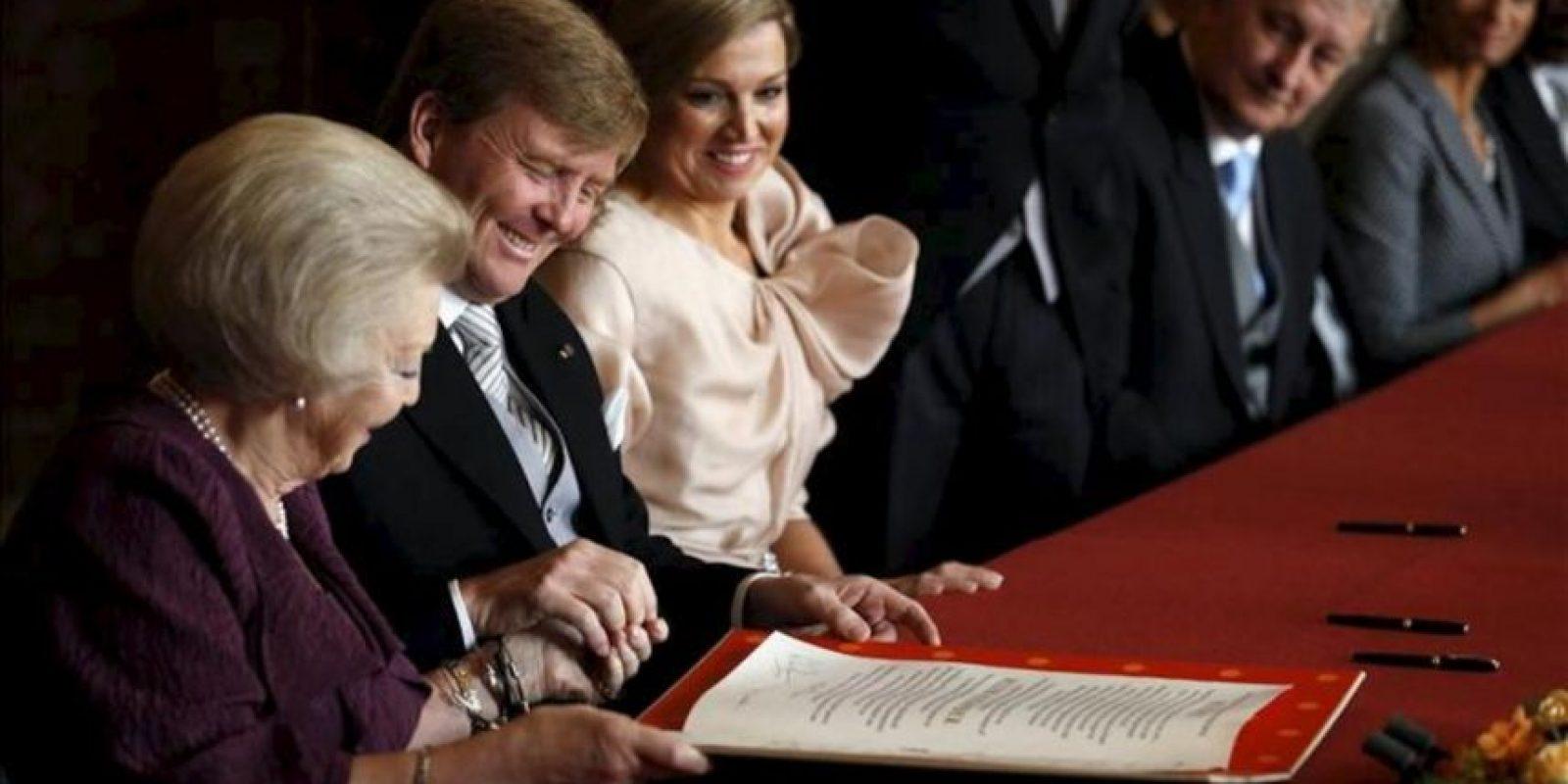 La reina Beatriz de Holanda (i), y el príncipe Guillermo-Alejandro, leen el acta de abdicación en presencia de la princesa Máxima (3-i), durante la ceremonia celebrada en el Moseszaal del Palacio Real de Ámsterdam, Holanda. EFE