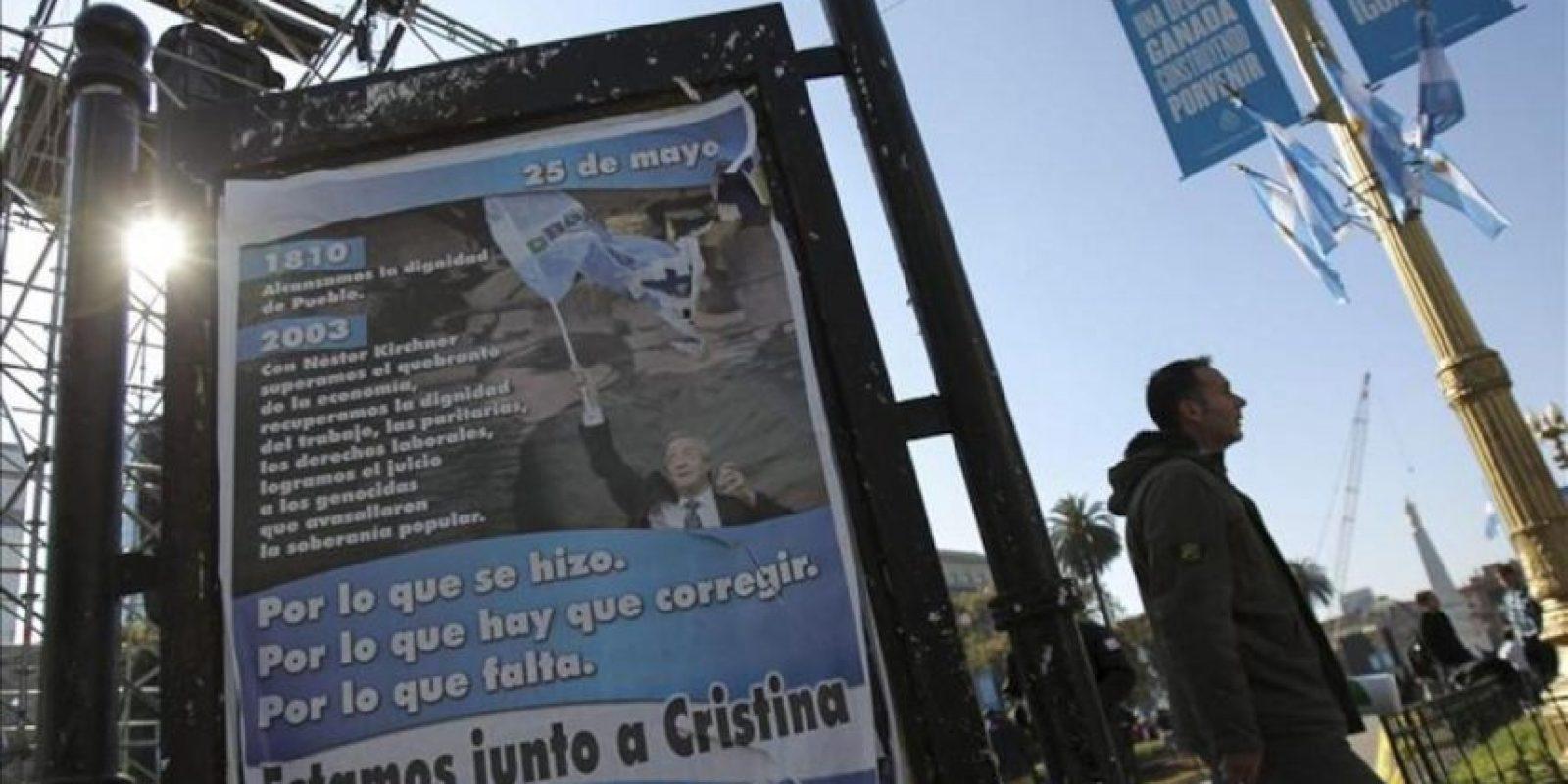 Un hombre fue registrado este viernes al caminar junto a un afiche promocional del fallecido expresidente Néstor Kirchner, en los alrededores de la Plaza de Mayo, en Buenos Aires. El oficialismo celebra los 10 años de la llegada de Kirchner al poder. EFE