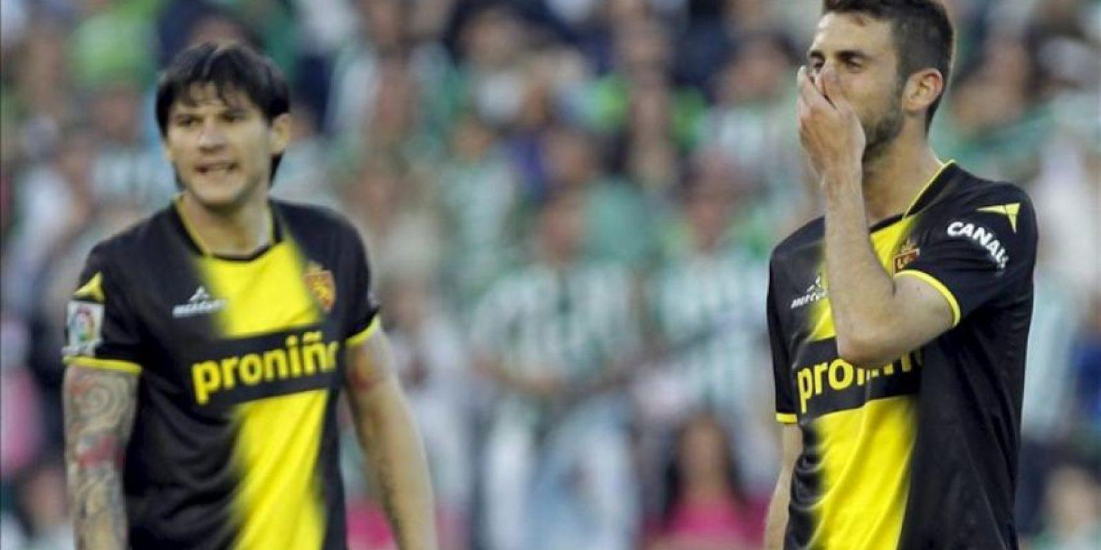 Los jugadores del Zaragoza Cristian Sapunaru (i) y José Marí Martín, tras encajar su equipo el tercer gol ante el Betis, en el partido de la trigésima séptima jornada de liga en Primera División en el estadio Benito Villamarín. EFE