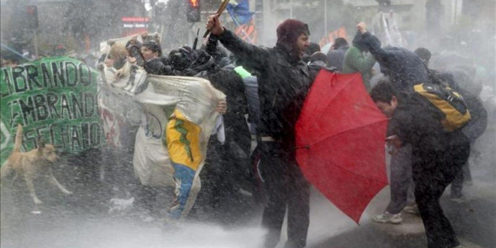 Varios manifestantes se protegen del vehículo lanzaaguas durante los incidentes en una marcha de estudiantes universitarios y secundarios hoy, martes 28 de mayo de 2013, en el centro de Santiago de Chile, donde la policía chilena disolvió con chorros de agua y gases lacrimógenos la protesta que no contaba con el permiso de las autoridades. EFE