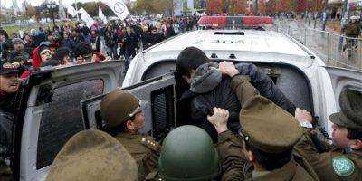 Policías detienen a un manifestante en una marcha de estudiantes universitarios y secundarios hoy, martes 28 de mayo de 2013, en el centro de Santiago de Chile, donde la policía chilena disolvió con chorros de agua y gases lacrimógenos la protesta que no contaba con el permiso de las autoridades. EFE