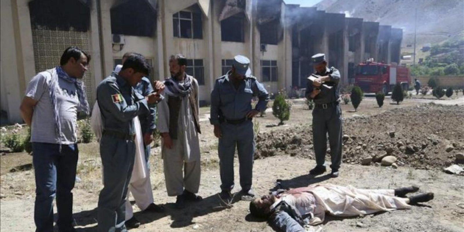 Varios policías afganos permanecen junto al cadáver de uno de los talibanes implicados en un ataque contra la residencia del gobernador de la provincia de Panjshir, en el norte de Afganistán. EFE