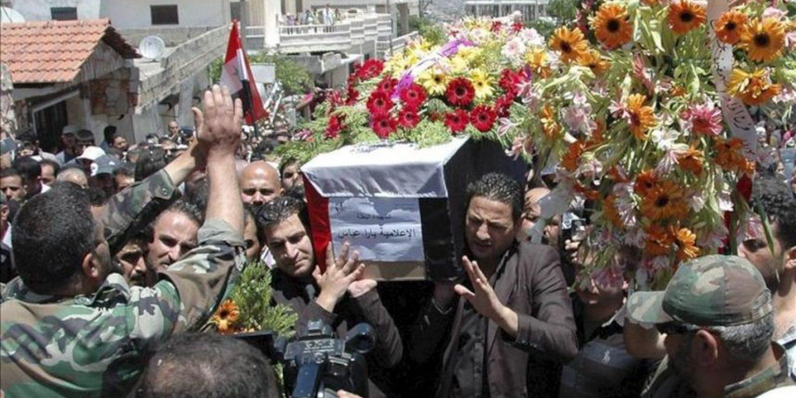 Ciudadanos sirios portan el féretro de la periodista de un canal de televisión que fue asesinada el lunes en Homs. EFE