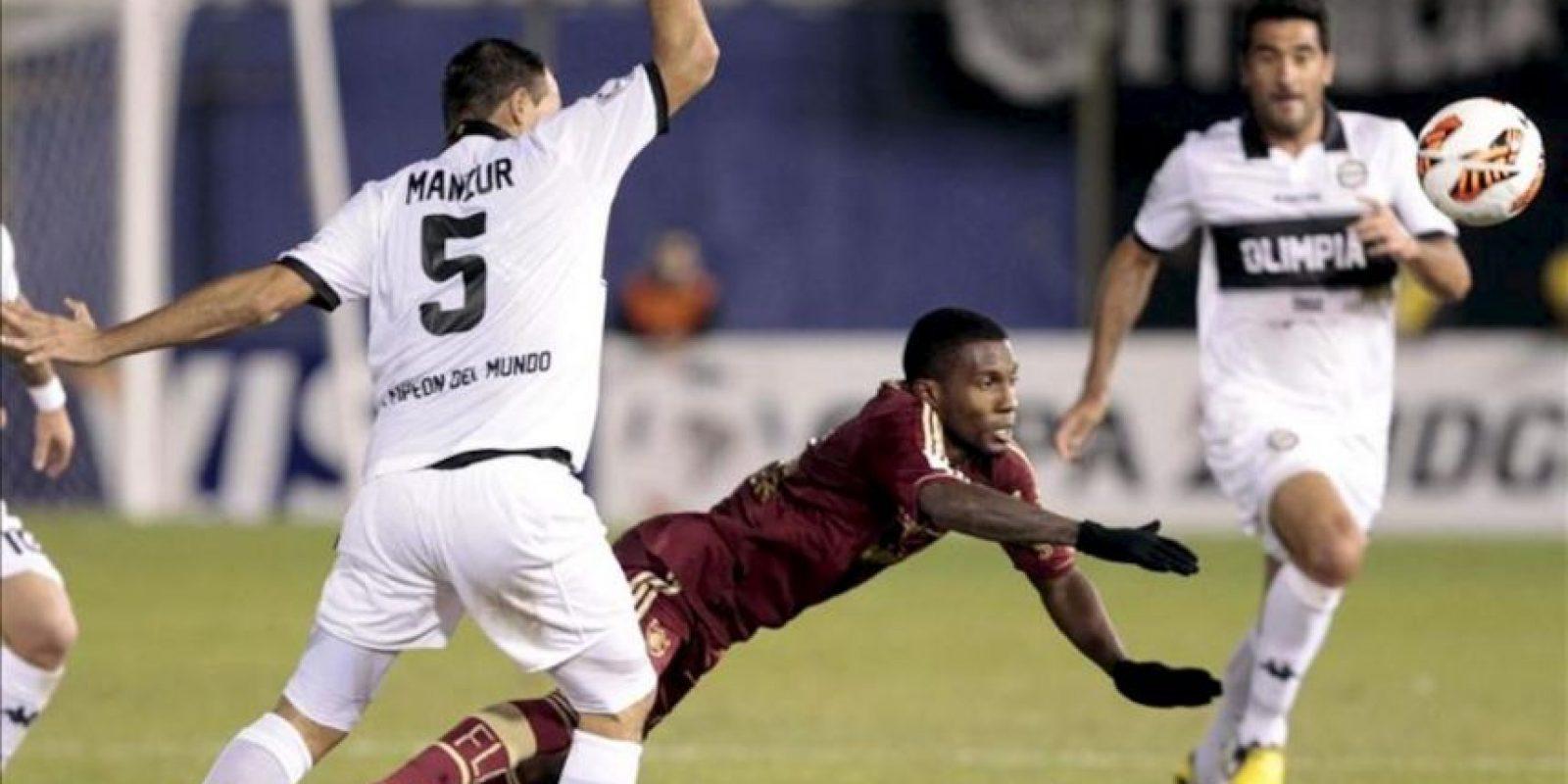 El jugador de Fluminense Rhayner (c) disputa el balón con Julio Manzur (i) y Juan Carlos Ferreyra (d), de Olimpia, durante un partido por los cuartos de final de la Copa Libertadores, en el estadio Defensores del Chaco, en Asunción (Paraguay). EFE