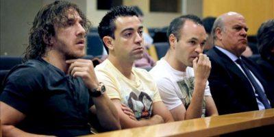 Los capitanes del F.C.Barcelona, Carles Puyol (i), Xavier Fernández (2i) y Andrés Iniesta (2d), junto al representante de Víctor Valdes, Ginés Carvajal (d), durante la rueda de prensa del portero titular del Barça, hoy en el Camp Nou, para argumentar su adiós del club cuando finalice su contrato, el 30 de junio del 2014. EFE