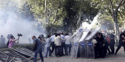 Antidisturbios turcos se escudan tras lanzar bombas de gas lacrimógeno contra los manifestantes durante una protesta contra la planeada construcción de un centro comercial en la Plaza Taksim, en Estambul, Turquía, hoy. EFE
