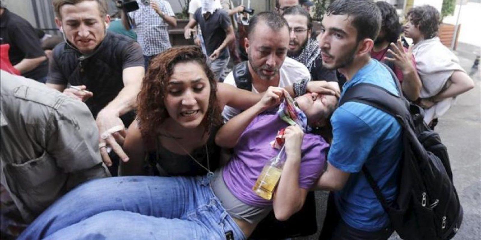 Una manifestante herida es evacuada por varios participantes durante una protesta contra la planeada construcción de un centro comercial en la Plaza Taksim, en Estambul, Turquía, hoy, viernes 31 de mayo de 2013. EFE