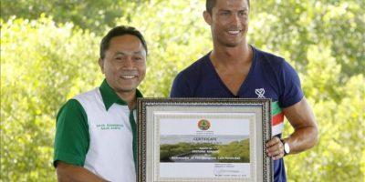 El delantero portugués del Real Madrid Cristiano Ronaldo (dcha) recibe un certificado como nuevo embajador del Foro para la conservación de los manglares de manos del ministro indonesio de Bosques, Zulkifli Hasan (izda), en Nusadua en Bali (Indonesia) hoy. EFE