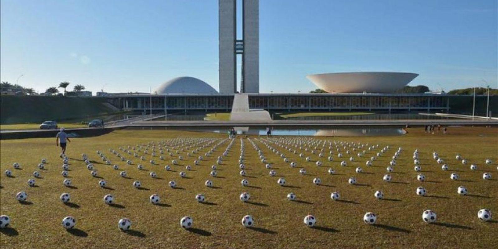 """Fotografía cedida por la Agencia Brasil el 26 de junio de 2013, que muestra cientos de balones de fútbol, que fueron """"sembrados"""" por la organización Río de Paz en el jardín del Congreso, en Brasilia (Brasil), para exigirles a cada uno de los legisladores que """"asuman su responsabilidad"""" ante la sociedad. EFE"""