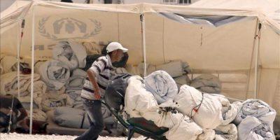 Un refugiado sirio transporta carpas en un campo de refugiados. EFE/Archivo