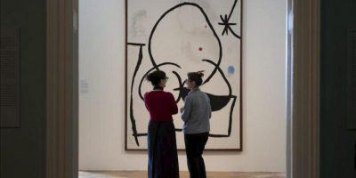 """Unas mujeres observan la obra """"Femme dans la nuit; Femme attrapant un oiseau"""" (1973)"""", del artista español Joan Miró, ayer durante la presentación para la prensa de la exposición """"Miró, Poésie et lumière"""" (Miró. Poesía y luz) en Lausana, Suiza. EFE"""