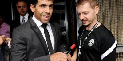 El nuevo futbolista del Juventus, el delantero argentino Carlos Tévez (izq), firma autógrafos antes de someterse a un reconocimiento médico en Turín (Italia) hoy. EFE