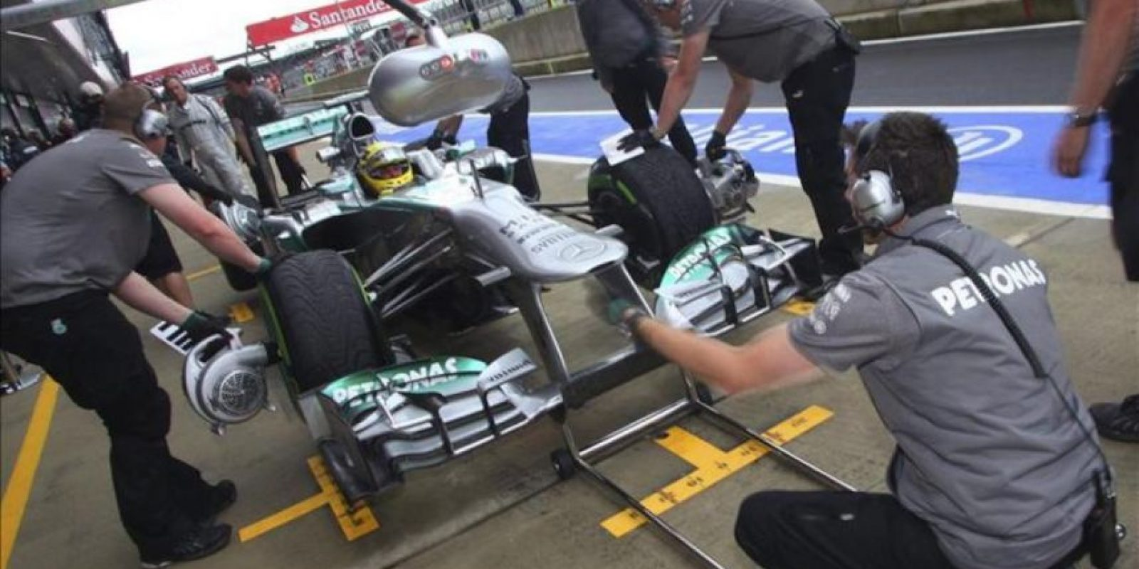 El monoplaza del piloto alemán Nico Rosberg (c), de Mercedes AMG, es revisado por los mecánicos de su escudería. EFE