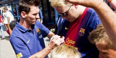 El delantero argentino del FC Barcelona, Lionel Messi (i), firma autógrafos a su llegada al aeropuerto de Oslo en Noruega, el 25 de julio de 2013. El FC Barcelona se enfrentará en partido amistoso al Valerenga Oslo el próximo 27 de julio. EFE