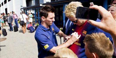 El delantero argentino del FC Barcelona, Lionel Messi (i), firma autógrafos, hoy a su llegada al aeropuerto de Oslo en Noruega. EFE