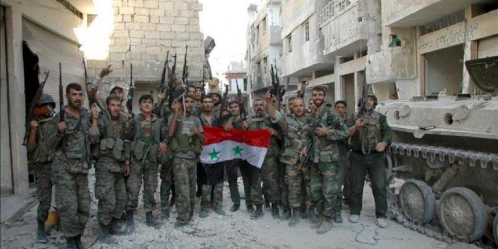 Soldados sirios posan con la bandera del país en los alrededores de al-Khalidyya, en Homs. EFE