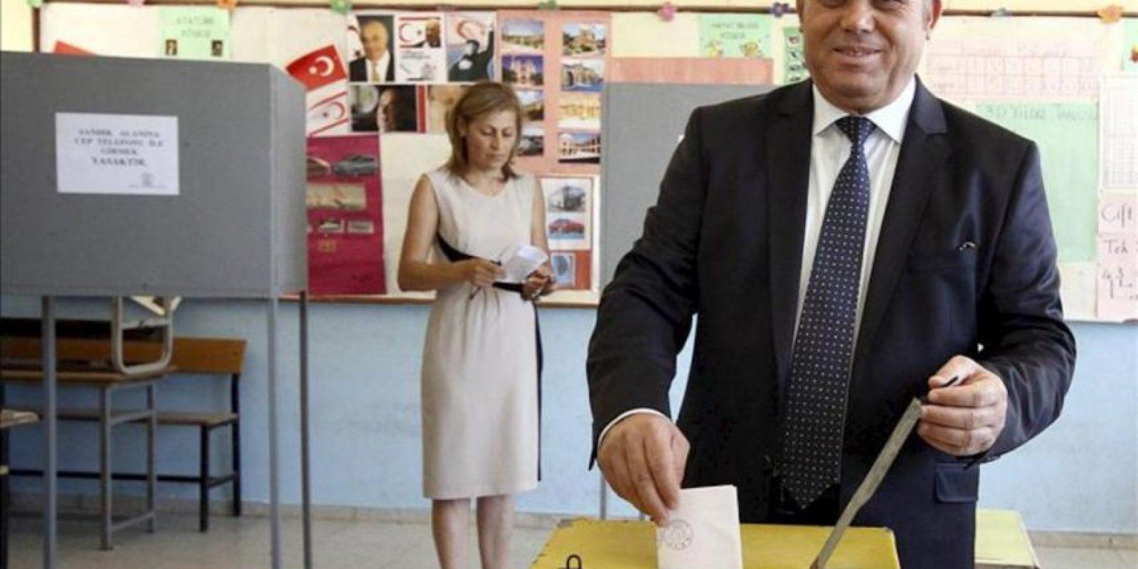 El político turcochipriota Ozkan Yorgancioglu (d) deposita su voto hoy en Nicosia. EFE
