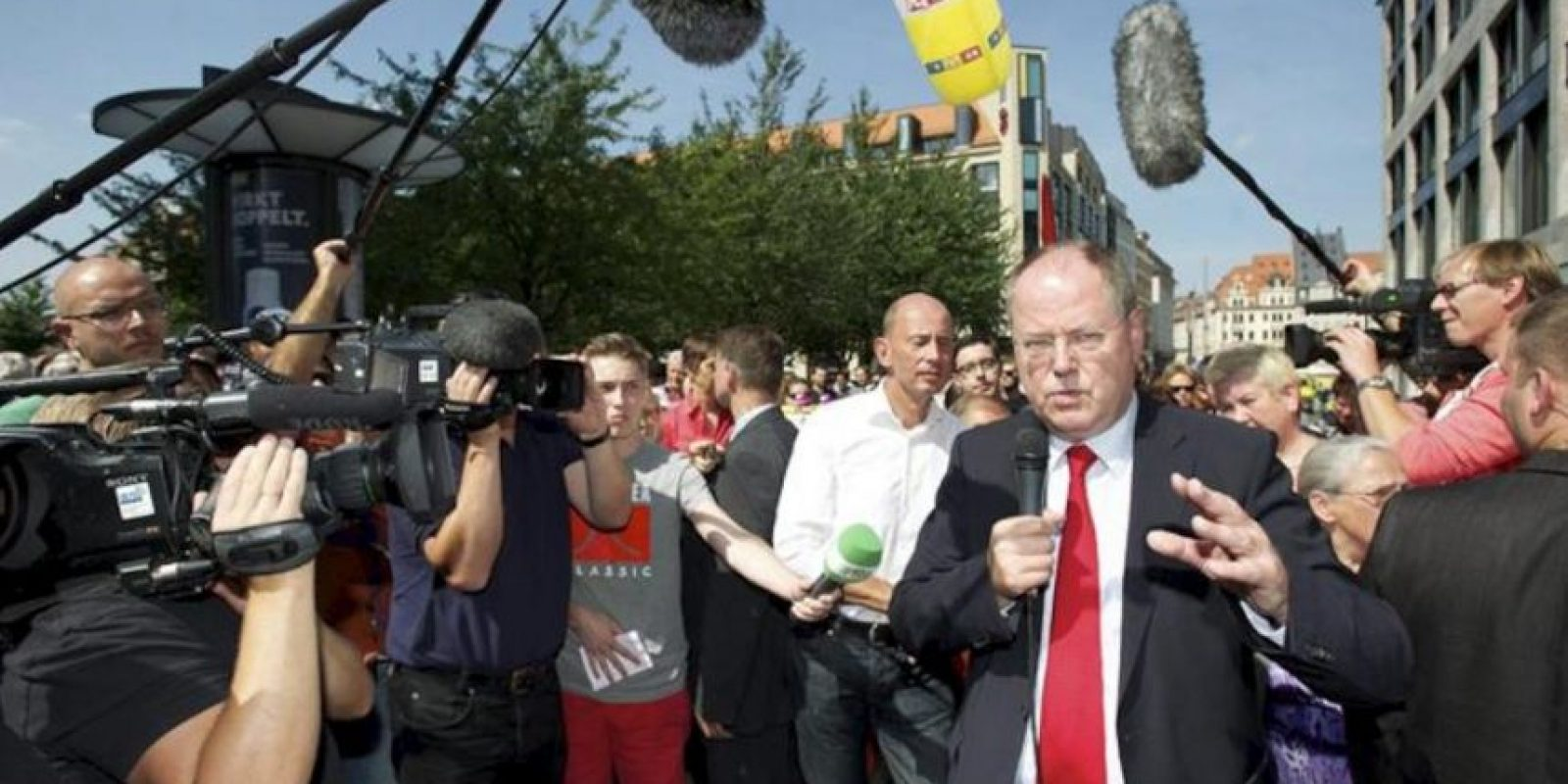 El candidato a canciller del Partido Socialdemócrata (SPD), Peer Steinbrueck (d), se dirige a su audiencia rodeado por los medios de comunicación en un puesto informativo del partido político en el centro de Leipzig, Alemania, el 22 de agosto de 2013. EFE