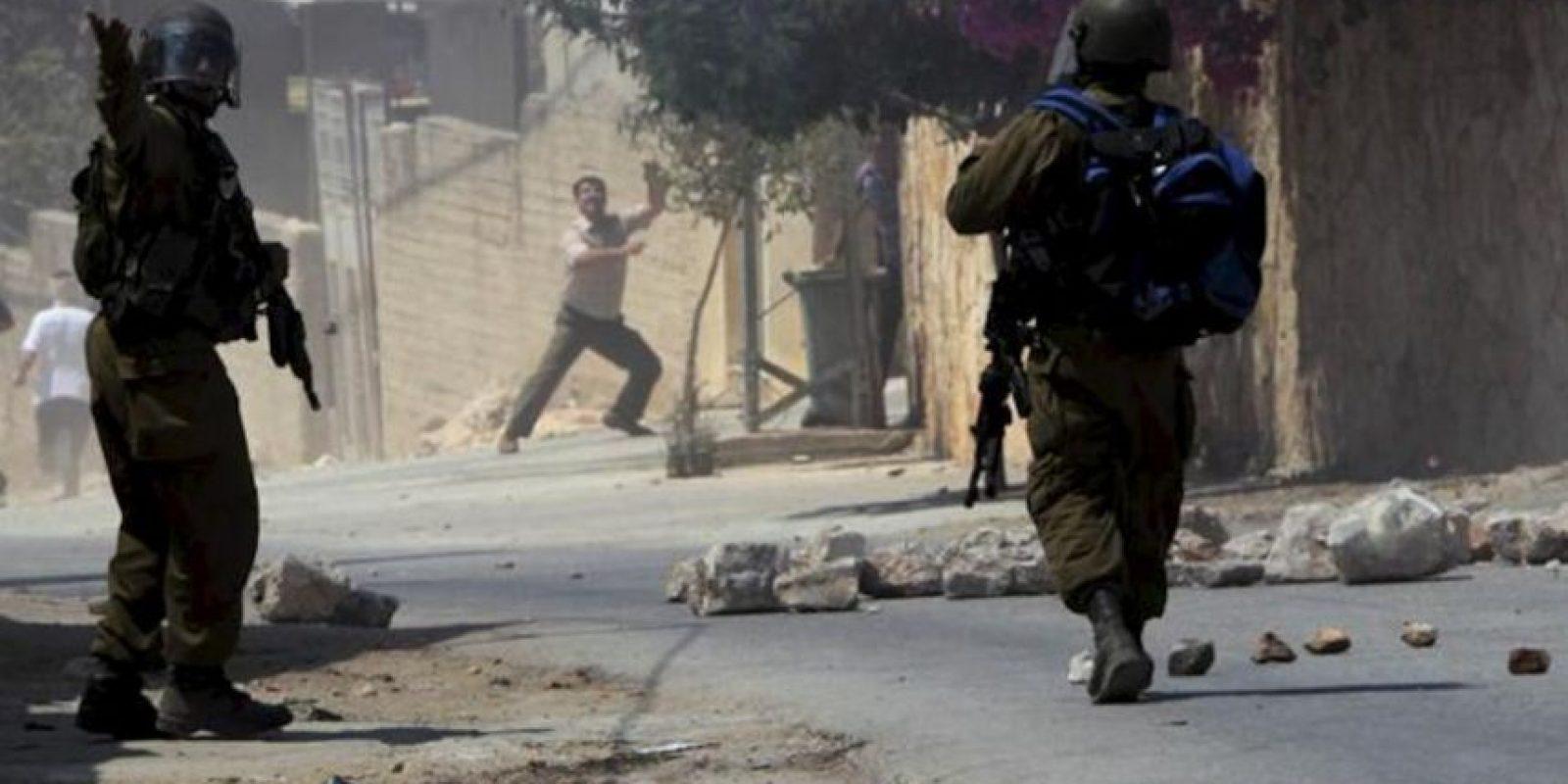 Varios soldados israelíes lanzan gas lacrimógeno contra manifestantes palestinos, durante la protesta semanal contra el asentamiento judío de Qadomem, cerca de la ciudad cisjordana de Nablus, hoy, viernes 23 de agosto de 2013. EFE