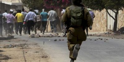 Un soldado israelí lanza gas lacrimógeno contra manifestantes palestinos, durante la protesta semanal contra el asentamiento judío de Qadomem, cerca de la ciudad cisjordana de Nablus, hoy, viernes 23 de agosto de 2013. EFE