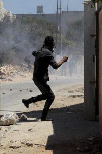 Un manifestantes palestino lanza piedras a las tropas israelíes, durante la protesta semanal contra el asentamiento judío de Qadomem, cerca de la ciudad cisjordana de Nablus, hoy, viernes 23 de agosto de 2013. EFE