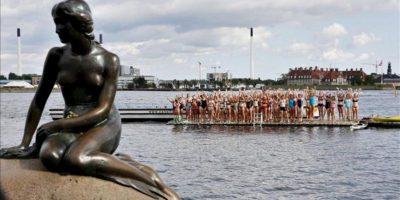 """Cien mujeres se preparan para realizar un 100 en el agua frente a la estatua """"La Sirenita"""" de Copenhague, Dinamarca. EFE"""