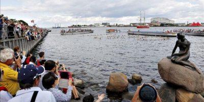 """Un grupo numeroso de turistas hacen fotos a las cien mujeres que, vestidas de """"sirenitas"""" han realizado un 100 en el agua frente a la estatua """"La Sirenita"""" de Copenhague, Dinamarca. EFE"""