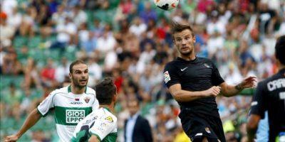 El delantero suizo de la Real Sociedad Haris Seferovic (d) despeja un balón de cabeza ante el defensa del Elche, David Lombán (i), durante el partido de la segunda jornada de la Liga BBVA que se ha disputado en el estadio Martínez Valero. EFE