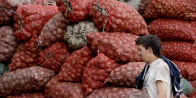 Un trabajador camina frente a sacos con alimentos en la Central de Abastos en Bogotá. Carreteras de nueve departamentos se mantienen bloqueadas, lo que ha reducido el traslado de productos a los mercados nacionales en el sexto día de huelga del sector agropecuario. EFE