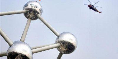 La bandera belga es colocada en lo alto del Atomium, el edificio que es el símbolo más famoso de Bélgica, en Bruselas. EFE/Archivo