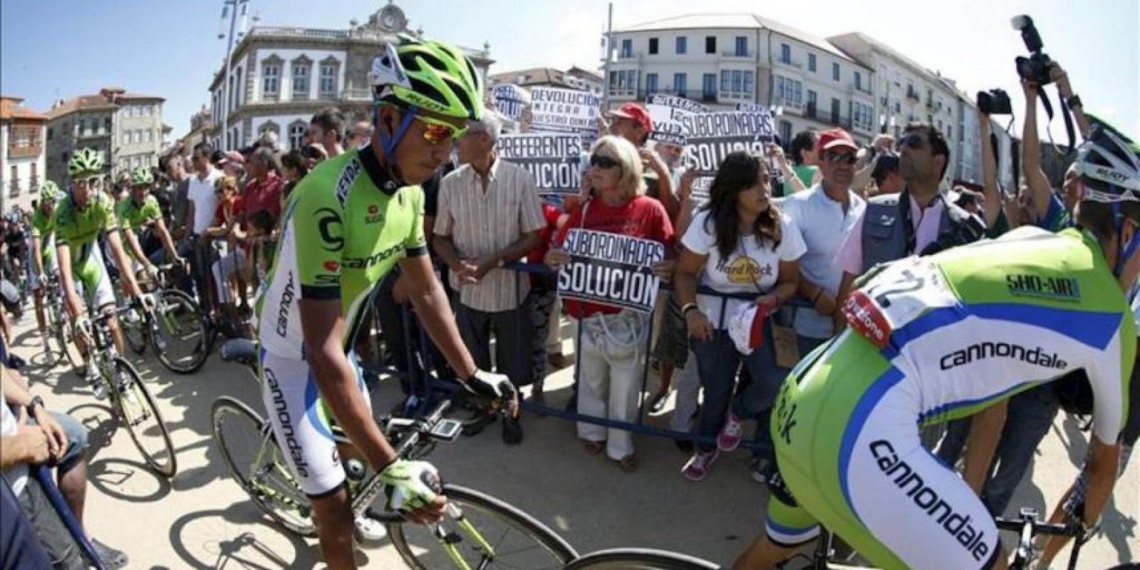 El pelotón de la Vuelta Ciclista a España se encaminan hacia la salida entre una protesta por las preferentes en Pontevedra donde se inició la segunda etapa con un recorrido de 177,7 kms.- EFE