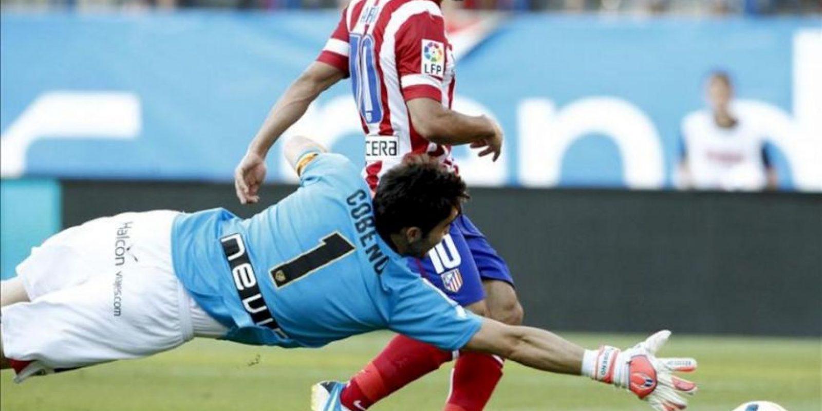 El jugador del Atlético de Madrid, Arda (d), bate al portero del Rayo Vallecano, Cobeño, en el partido de la Liga BBVA . EFE