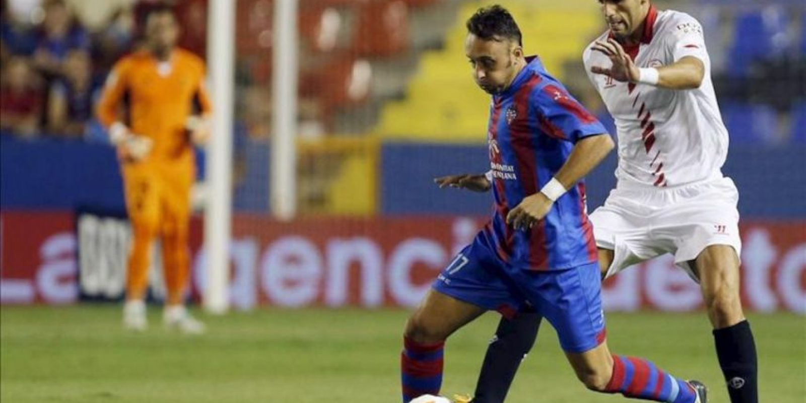 El jugador del Levante Xumetra (i) trata de escapar del argentino Fazio, del Sevilla, durante el partido de la Liga BBVA disputado en el estadio Ciutat de Valencia. EFE