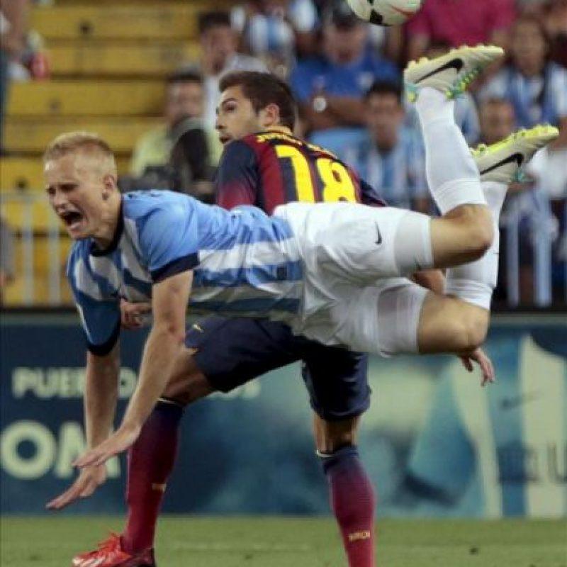 El delantero polaco del Málaga Bartlomiej Pawlowski (i) cae ante Jordi Alba, del FC Barcelona, durante el partido de la segunda jornada de Liga BBVA que se disputó en el estadio de La Rosaleda, en Málaga. EF