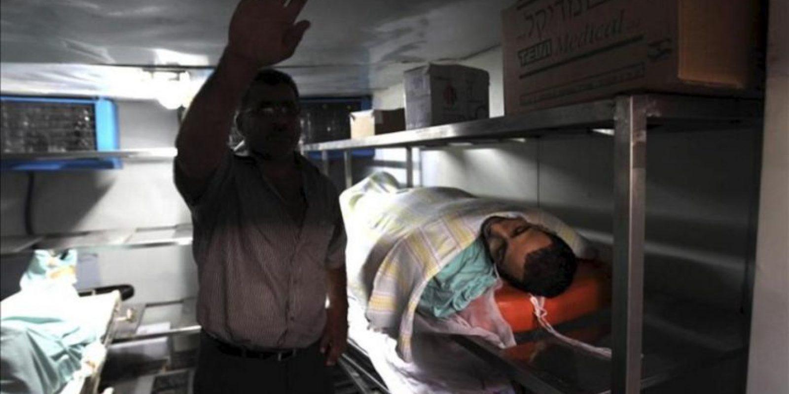 Un hombre permanece junto a los cuerpos de los tres palestinos muertos por fuego del ejército israelí en el campo de refugiados de Kalandia, a las afueras de la localidad cisjordana de Ramala (Palestina). EFE
