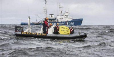"""Fotografía facilitada por Greenpeace que muestra a miembros de Greenpeace protestando frente a un barco de la guardia fronteriza rusa en el Océano Ártico. Los agentes fronterizos detuvieron el barco después de que los activistas (de Greenpeace) desembarcaran desde el """"Arctic Sunrise"""" y se acercaran con lanchas neumáticas al barco de exploración sísmica """"Geolog Dmitri Nalivkin"""", fletado por la petrolera rusa Rosneft y la estadounidense ExxonMobil, con pancartas """"¡Salven el Ártico!"""". EFE/Will Rose"""