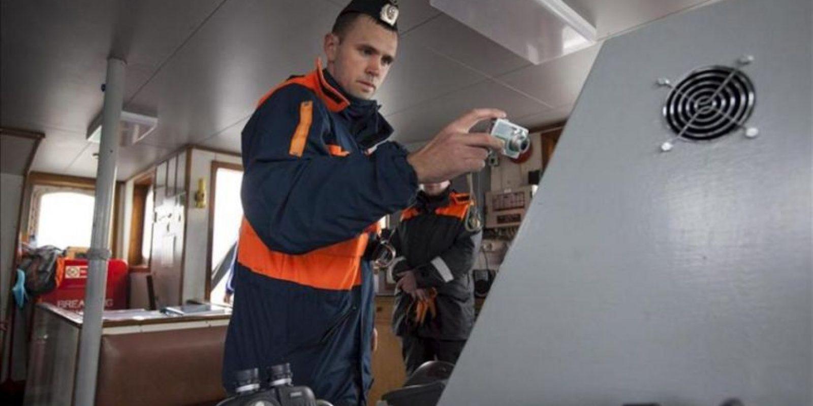 Fotografía facilitada por Greenpeace que muestra a un agente de la guardia fronteriza rusa tomando fotografías a bordo del rompehielos de Greenpeace en el Océano Ártico. EFE/Will Rose