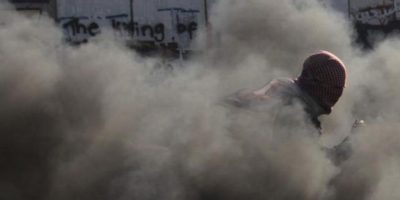 Un manifestante palestino corre entre el humo durante los disturbios con la policía israelí en el punto de control de Kalandia, en la localidad cisjordana de Ramala hoy 26 de agosto de 2013. EFE