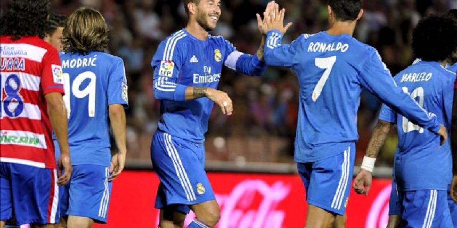 El delantero portugués del Real Madrid Cristiano Ronaldo (d) celebra con el defensa Sergio Ramos (3i) el gol que acaba de marcar su compañero Karim Benzema, el primero de su equipo en el encuentro ante el Granada, correspondiente a la segunda jornada de la Liga BBVA de Primera División. EFE
