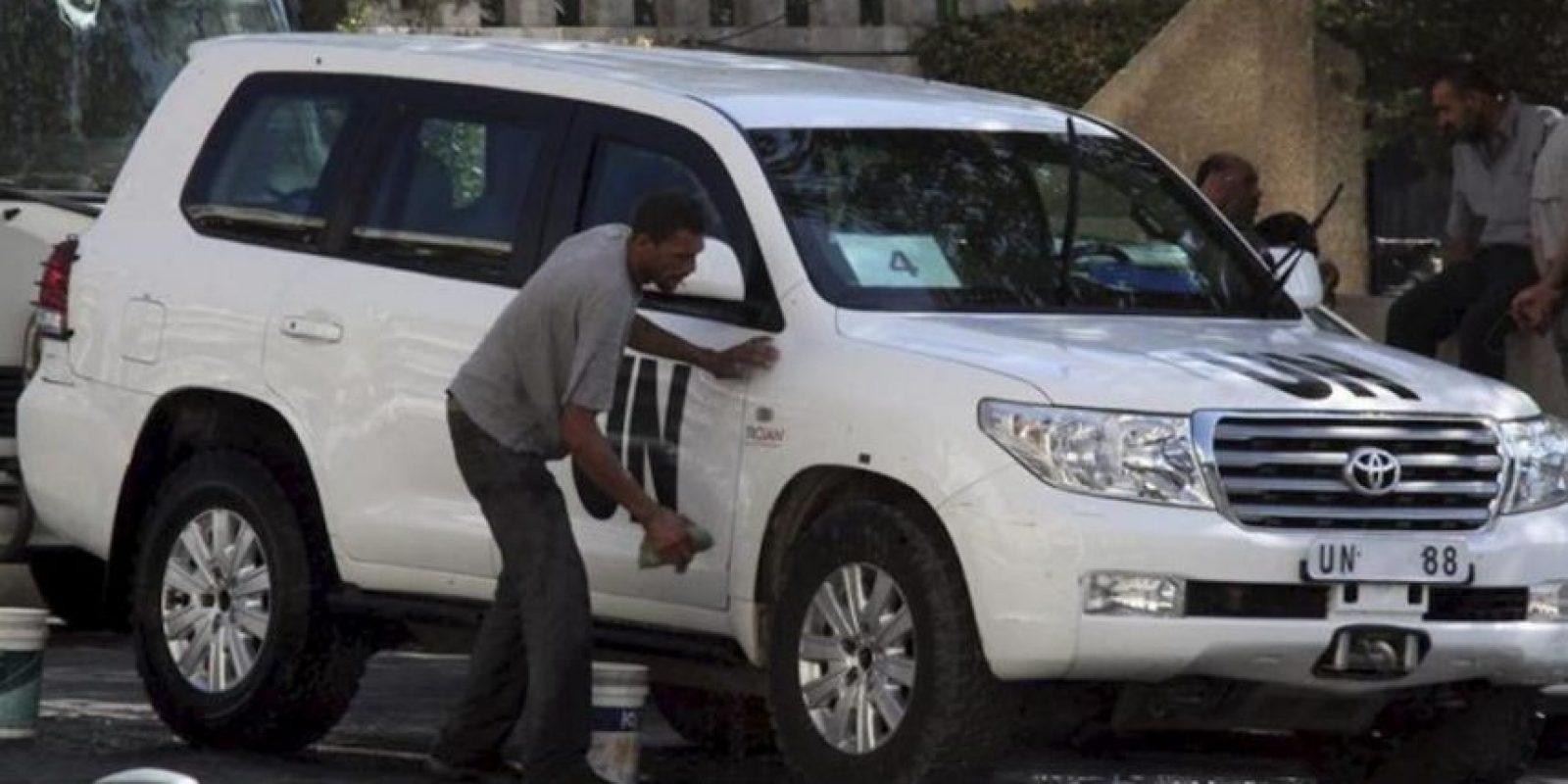 Un operario sirio limpia uno de los coches usados por la misión de inspectores de la ONU delante del hotel Four Seasons de Damasco (Siria). EFE