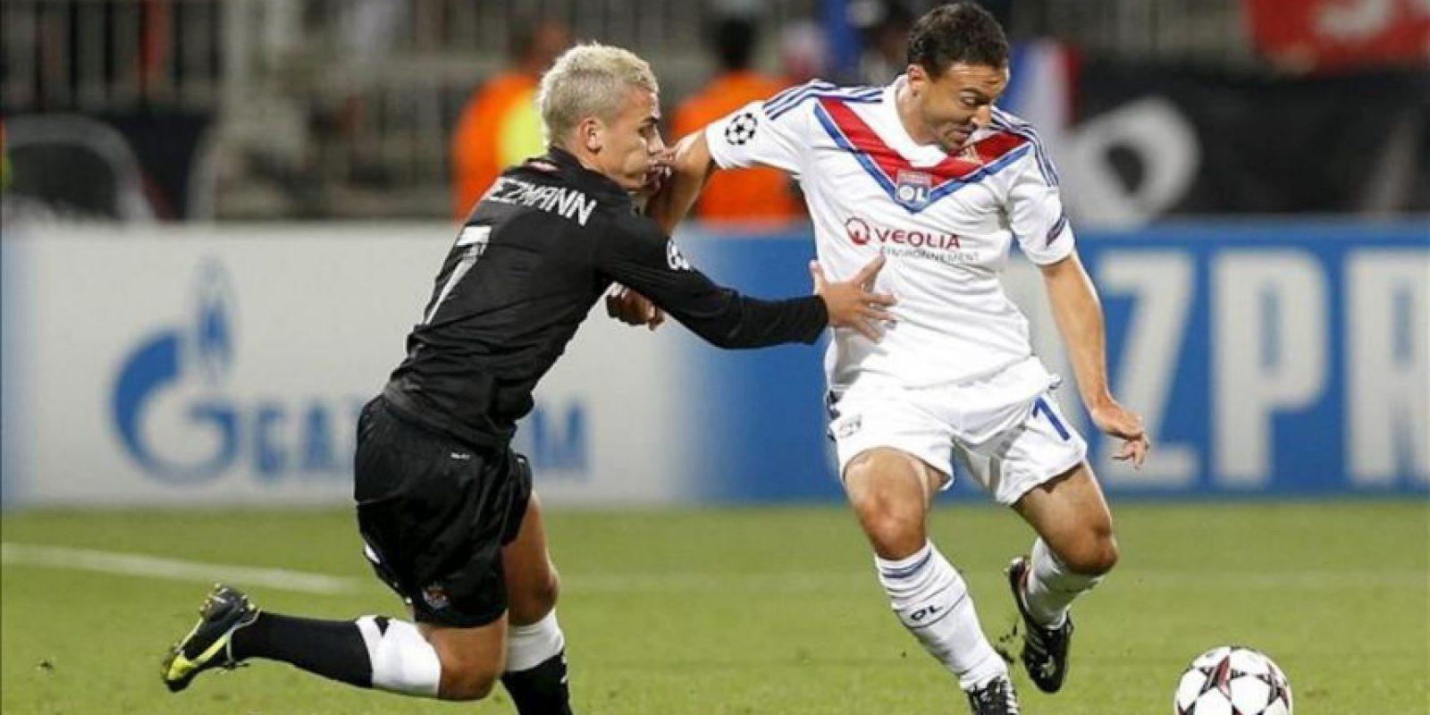 El jugador francés de la Real Sociedad, Antoine Griezmann (izda), pelea por el control del balón con el jugador del Olympique de Lyon, Steed Malbranque, durante el partido de clasificación para la Liga de Campeones disputado en el estadio Gerland de Lyon (Francia). EFE/Archivo
