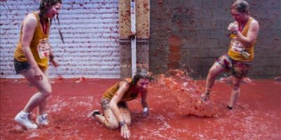 Tres jovenes participan en la fiesta de la Tomatina, una guerra a tomatazos en la que se lanzan durante una hora 130.000 kilos de tomate por las calles de la pequeña localidad española de Buñol (Valencia). EFE