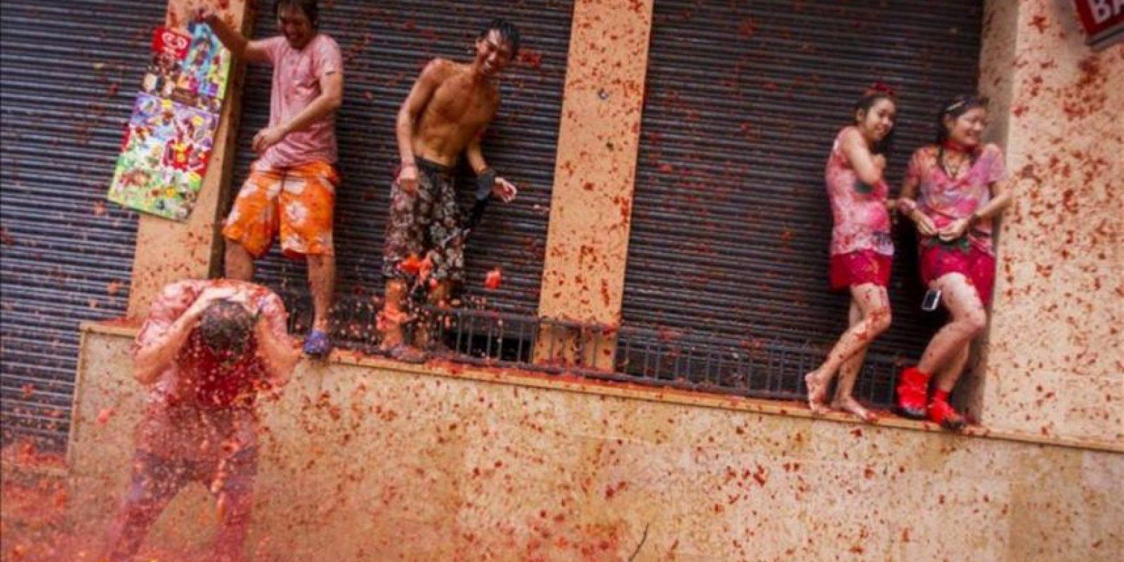 Una persona participa en la fiesta de la Tomatina, una guerra a tomatazos en la que se lanzan durante una hora toneladas de tomate por las calles de la pequeña localidad valenciana de Buñol. EFE