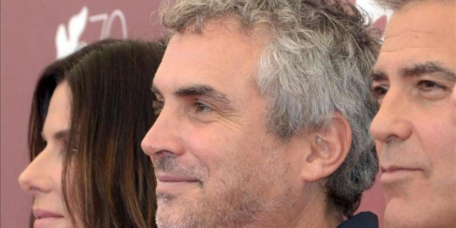 """Los actores estadounidenses George Clooney (d) y Sandra Bullock (i), posan junto al director mexicano Alfonso Cuarón (c), durante el pase gráfico de la presentación de la película """"Gravity"""", un thriller dirigido por Cuarón, durante la 70 edición del Festival de Cine de Venecia. EFE"""