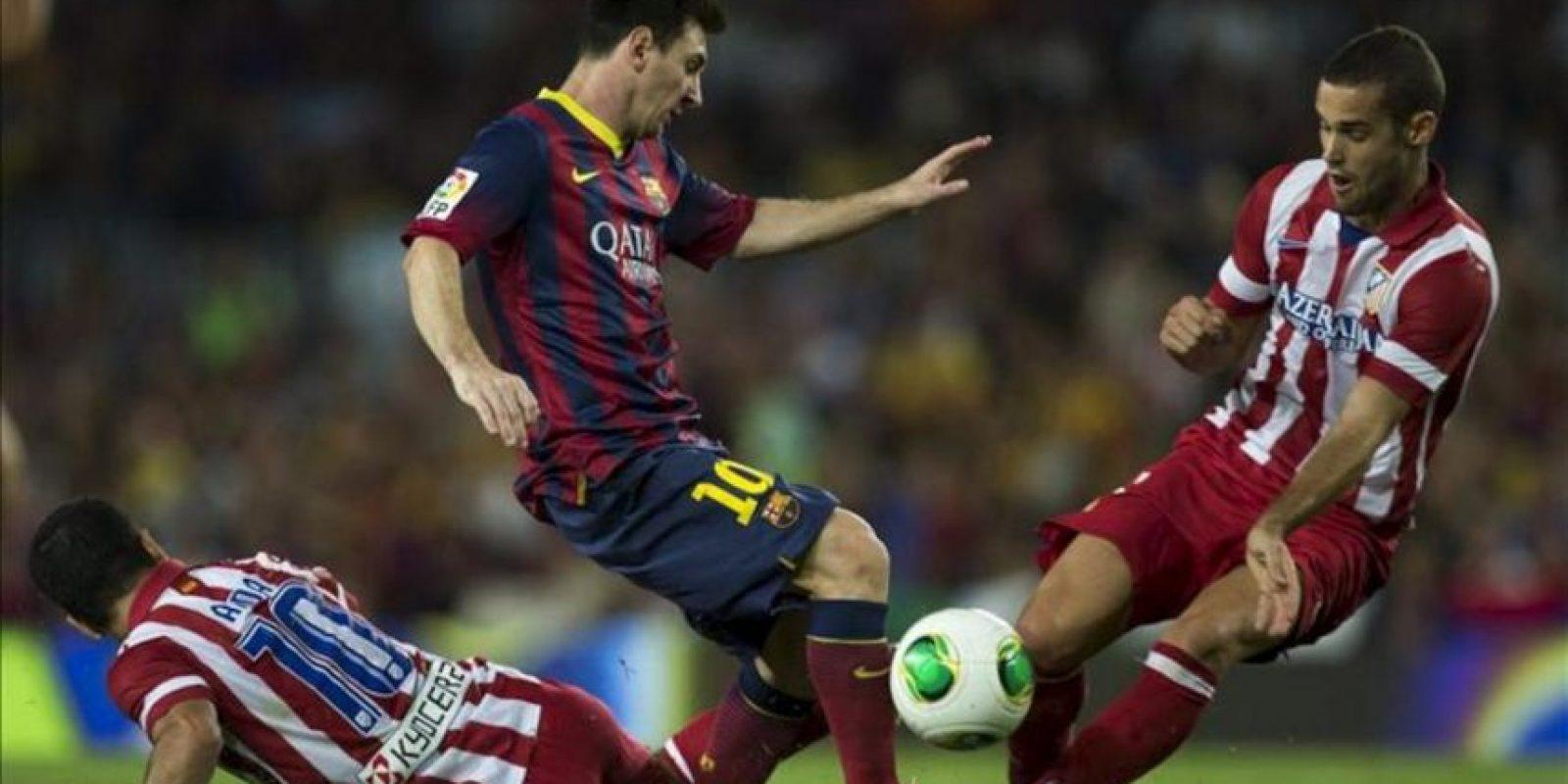 El delantero argentino del FC Barcelona, Leo Messi (c), lucha el balón junto al turco Arda Turan (i) y Mario Suárez (d), del Atlético de Madrid, durante el partido de vuelta de la Supercopa de España que los dos equipos disputaron en el Camp Nou, en Barcelona. EFE